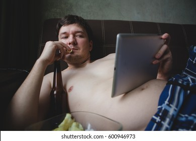 a lazy man watching a sports game on a tablet computer at home while drinking beer