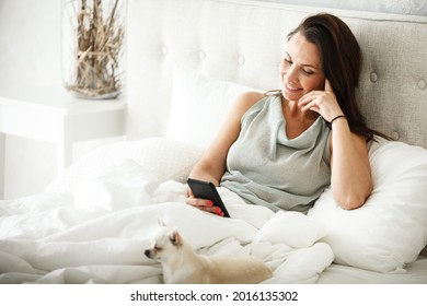 Lazy morning concept. Beautiful happy woman wakes up in bed and surfes internet on phone. Attractive female lying and resting at home in bedroom. Little dog sleeps near on white sheets