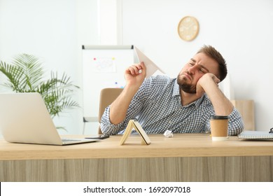 Lazy office employee playing with paper plane at workplace