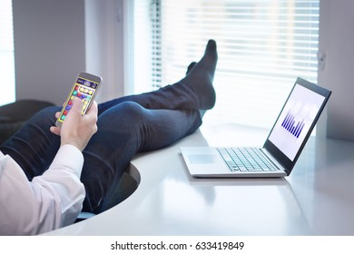Lazy office worker playing mobile game with smartphone during work hours. Avoiding his job and being lazy with feet and socks on table. Useless and relaxing man doing nothing and forget his job.