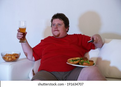 Lazy overweight male sitting with glass of beer on couch and watching television