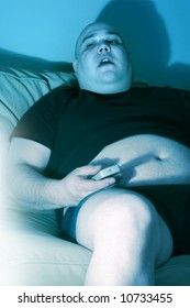 Lazy overweight male sitting on a couch watching television.  Harsh blue lighting from television with slow shutter speed to create TV watching atmosphere.