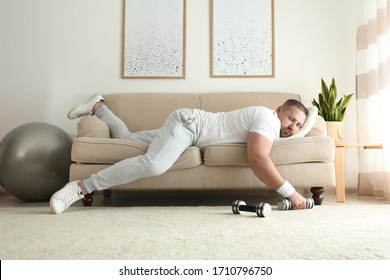 Lazy overweight man with dumbbells sleeping on sofa at home