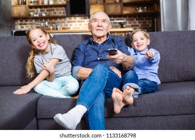 Lazy rest. Pleasant aged man holding a remote control while watching TV with his grandchildren