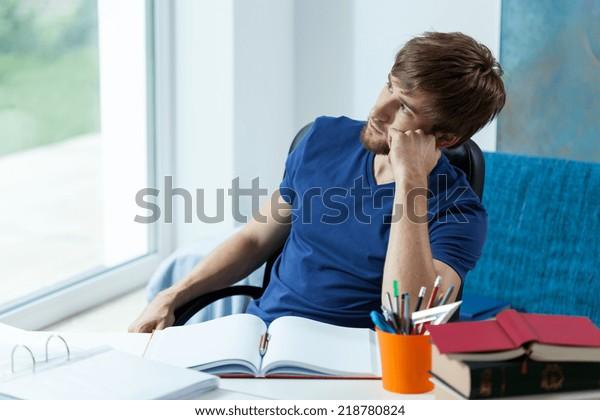 Schöner Schüler, der durch das Fenster in seinem Studienzimmer schaut