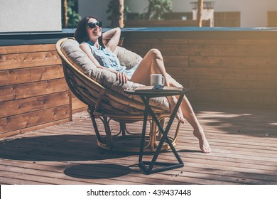 Lazy time in comfortable chair. Beautiful young woman relaxing in a big comfortable chair on her outdoor house terrace