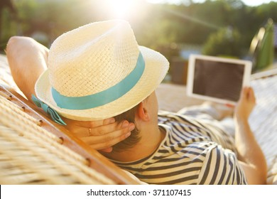Lazy time. Man in hat in a hammock with tablet computer on a summer day