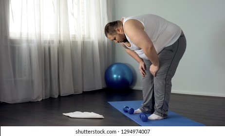 Lazy unmotivated man throwing dumbbells on floor, hopelessness, insecurities