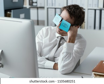 Lazy unproductive office worker wearing funny sticky notes on his glasses and hiding his closed eyes
