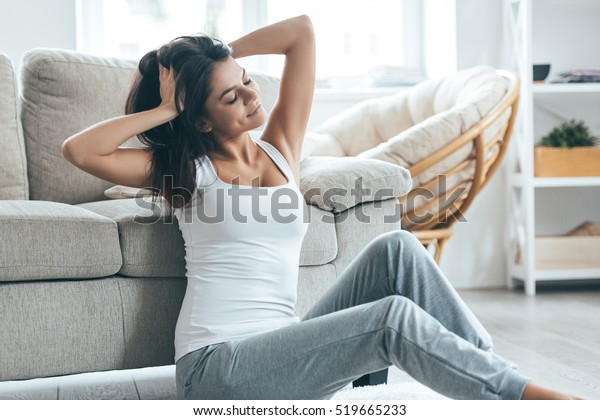 Lazy weekend. Attractive young woman sitting on the carpet at home and holding hands in hair
