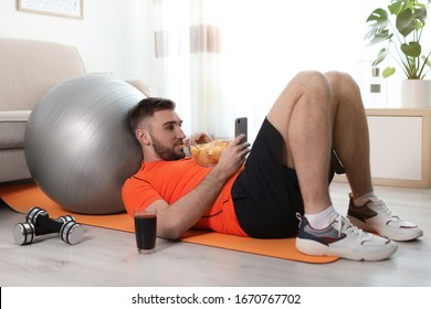 Lazy young man with smartphone eating junk food on yoga mat at home