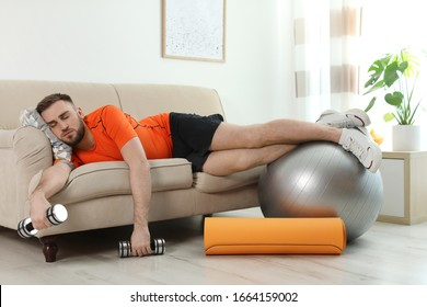 Lazy young man with sport equipment on sofa at home