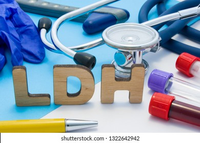 LDH Medical lab acronym, meaning lactate dehydrogenase. Letters that make word of LDH, located near test tubes with blood, stethoscope and other diagnostic tools and devices, latex gloves