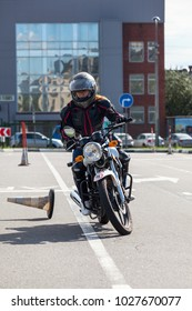 L-driver motorcyclist doing exercises with cones on asphalt ground
