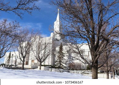 The LDS Mormon temple in Bountiful Utah with trees, snow and blue sky