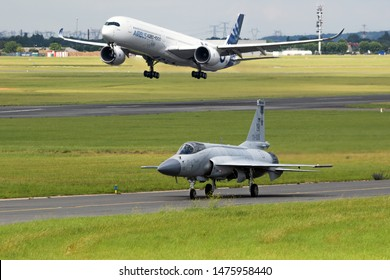 LE BOURGET PARIS - JUN 20, 2019: Pakistan Air Force JF-17 Thunder fighter jet taxiing while an Airbus A350 XWB passenger plane landing after it's performance at the Paris Air Show.