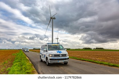 Le Gault-Saint-Denis, France - October 08, 2017: The official ambulance driving on a road in the plain with windmills in a cloudy day during the Paris-Tours road-cycling race.