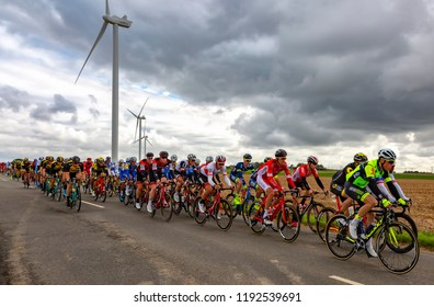 Le Gault-Saint-Denis, France - October 08, 2017: The peloton riding on a road in the plain with windmills in a cloudy day during the Paris-Tours road-cycling race.