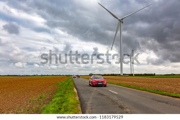 Le Gault-Saint-Denis, France - October 08, 2017: The breakaway is approaching on a road in the plain with windmills in a cloudy day during the Paris-Tours road-cycling race.