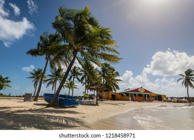 Le Gosier, Guadeloupe - December 20, 2016: Paradise Lovely beach, palm trees and shop near Le Gosier in Guadeloupe, an overseas region of France, Lesser Antilles, Caribbean.
