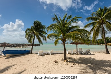 Le Gosier, Guadeloupe - December 20, 2016: Tropical beach with palm trees, umbrellas and sunbeds near Le Gosier in Guadeloupe, an overseas region of France, Lesser Antilles, Caribbean.