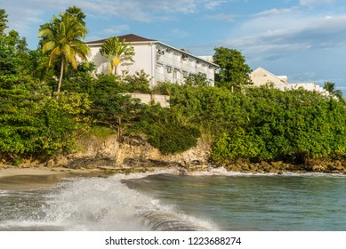 Le Gosier, Guadeloupe - December 21, 2016: Built, Coconut Palm Trees and and picturesque rocky coast near Le Gosier, Guadeloupe, an overseas region of France, Lesser Antilles, Caribbean.