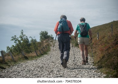 Le grand Ballon, France - 27 August 2017 - couple of trekkers walking at the top with backpack