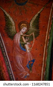 LE MANS, FRANCE - AUGUST 2, 2018: Angel playing at harp . Detail of fresco painted on the vaults of the chapel of the Virgin in Saint -Julien cathedral.