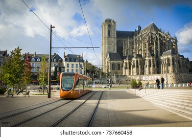LE MANS, FRANCE - OCTOBER 08, 2017: Roman cathedral of Saint Julien with an orange tram at a Le mans Sarthe, Pays de la Loire, France