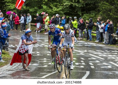 LE MARKSTEIN, FRANCE - JUL 13:A fan cheers a group of three cyclists on the road to mountain pass Le Markstein during the stage 9 of Le Tour de France on July 13, 2014.