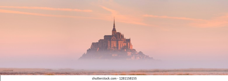 Le Mont Saint Michel in Normandy, France on a foggy morning at sunrise.