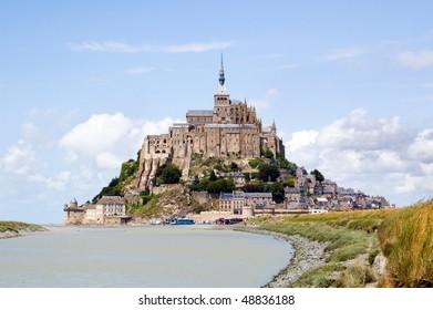 Le Mont Saint Michel on horizon under blue sky, Normandie, France