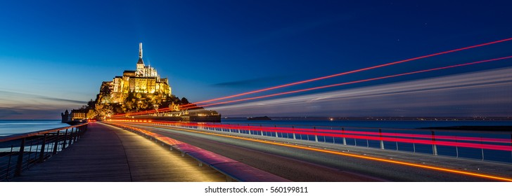 Le Mont saint michel Panoramic of famous historic Illuminated architecture panoramic beautiful postcard view with red light trail at Night in Summer Low Tide from the bridge with reflection, France