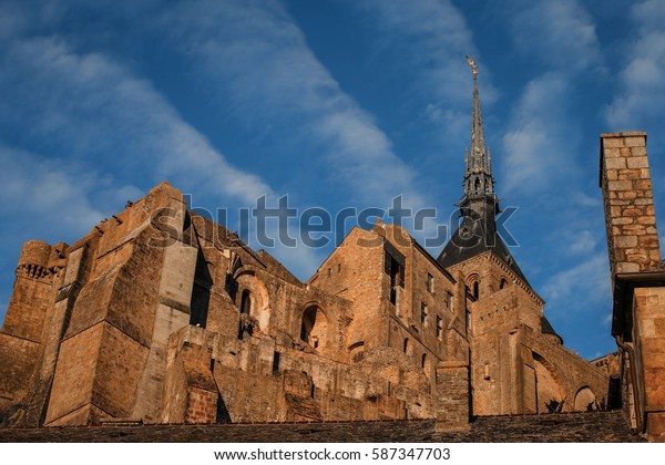Le Mont Saint-Michel is a rocky tidal island in Normandy with blue sky, it is one of the most visited tourist sites in France.
