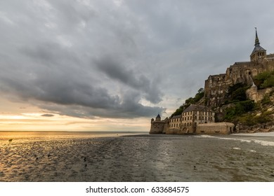 Le mont Saint-Michel at sunset with low tide and menacing cloudy sky