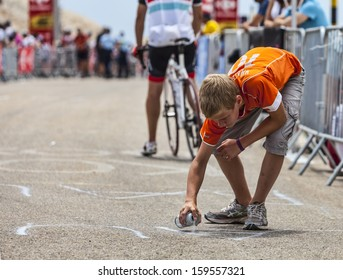 LE MONT VENTOUX, FRANCE-JUL 14:Boy painting the road to Mont Ventoux while amateur cyclists climb few hours before the apparition of the cyclists during the stage 15 of Tour of France on July 14 2013