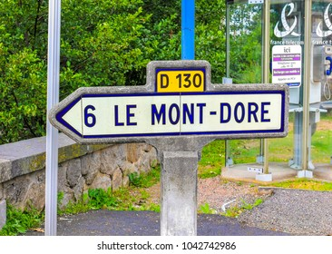 LE MONT-DORE, FRANCE - JULY 28, 2011: A vintage road sign indicates the direction of the town of Le Mont-Dore, located in central France. Le Mont-Dore is famous for its thermal springs and ski resort.