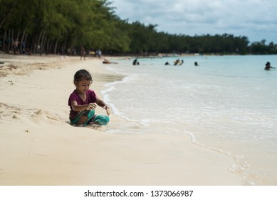 Le Morne beach / Mauritius - 08.01.2019: Local girl enjoying the tropical beach along with tourists from all over the world.