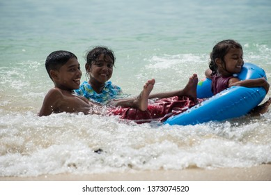 Le Morne beach / Mauritius - 08.01.2019: Local children enjoying the tropical beach along with tourists from all over the world.