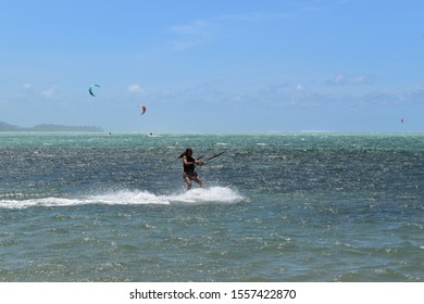 Le Morne, Mauritius, 10th of November 2019. Picture of an unknown girl riding a kite surf in a rough sea. Water sport background.
