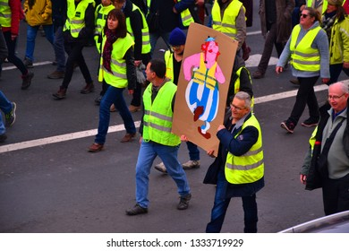 """Le Puy-en-Velay, France - March 9th 2019 : French """"gilets jaunes"""" (Yellow vests) in the street. Focus on two men carrying a sign with the hero Obelix on it."""