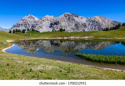 Le Rois Mages (Baltazar 3153m, Melchior 2948 m, Gaspard 2808 m , Quatre Soeurs 2587 m) and their reflection in the lake Chavillon on Etroite Valley- Hautes-Alpes.