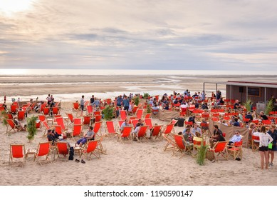 LE TOUQUET, FRANCE. AUG. 11, 2018. Beach bar with people sitting on beach chairs with together with friends. Sunset at the beach in Le Touquet Paris Plage, France.