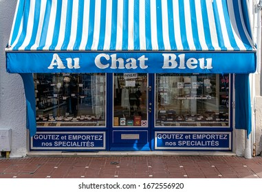 LE TOUQUET, FRANCE - MARCH 13, 2020. Confectionery and chocolate shop: AU CHAT BLEU. At the bottom of the window is indicated in French: Taste and take away our SPECIALTIES.