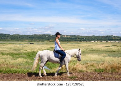 LE TOUQUET PARIS PLAGE, FRANCE. Aug 11 2018. Girl on horse riding classes in Summer. Girl on horse at Bay of Clanche near Le Touquet Paris Plage and Etaples on French coast. Le Touquet, France.