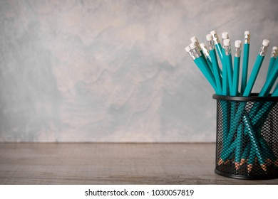 lead blue pencils in black metal holder pot on a beton background