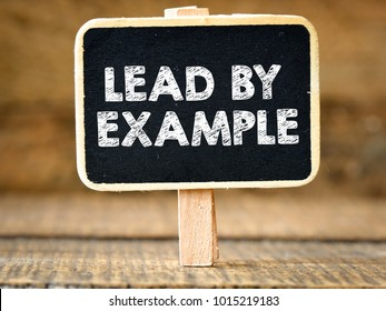 Lead by example. Business concept on blackboard on wooden background