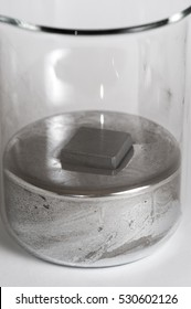 Lead cube floats in a beaker of mercury.