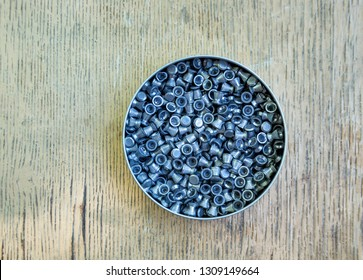 Lead pellets in metal box for pneumatic weapons on background of the old old painted board, for sport and hunting