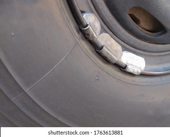 Lead weight on car rims. Lead-weighted wheel balancing for vehicle wheel balance while in use with copy space. Focus close and choose the subject.